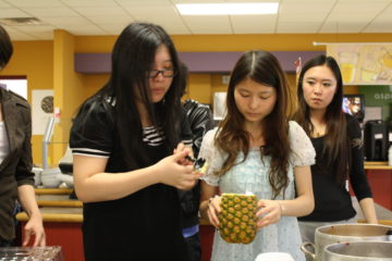 Jinglin Chen, accounting sophomore, and Lu Yu, digital arts junior, prepare dish at the International Cuisine Night April 15 in the cafeteria. Hanyuan Yin, business sophomore, looks on. A variety of food was prepared from different nationalities for everyone to taste.