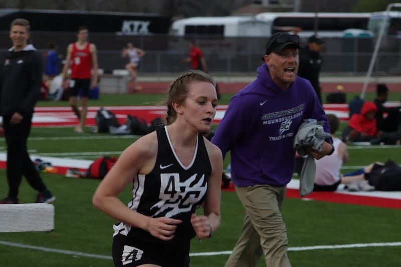 Erin Floyd, early childhood education junior, quickens her pace after Tim Testa, head track and cross country coach, cheers her on. Erin placed 6th overall in the 3000M steeple chase with a time of 12:34.73.