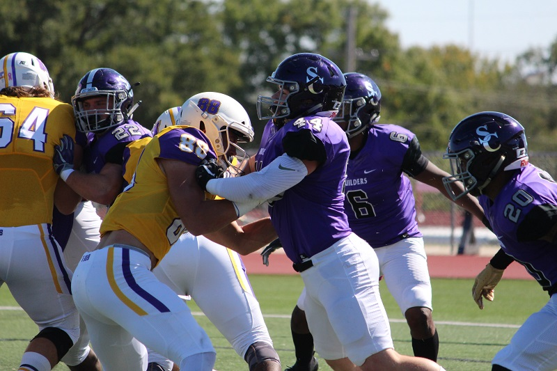 Clayton Downum, junior linebacker, blocks Kansas Wesleyan's Trenton Poe-Evans, senior wide receiver, during a Coyote offensive play. Before the day's KWU win, the Coyotes were ranked second in the KCAC. (Tessa Castor/Staff photographer)