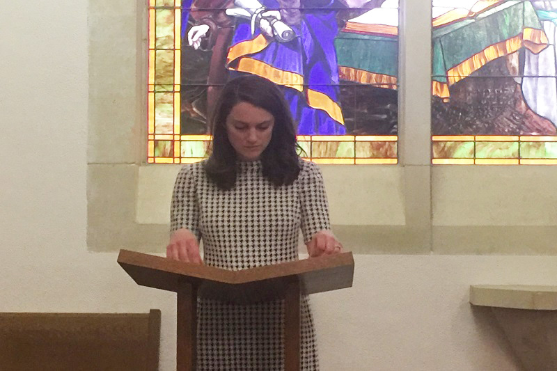 """Molly Just, director of discipleship and campus minister, reads the final scripture after a moment of silence. The final scripture read was John 14:1-4, 18-19, 27 - """"Do not let your hearts be troubled. You believe in God; believe also in me,"""" John 14:1. (Emily Berry/Staff photographer)"""