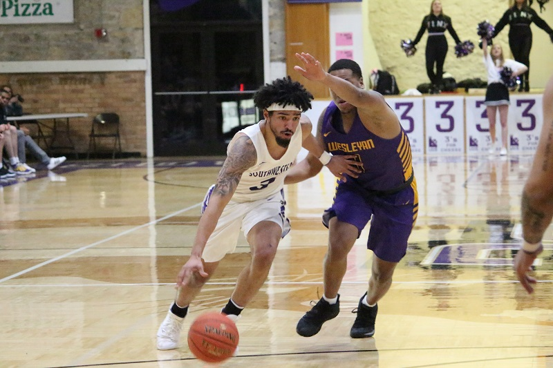 ABOVE: Jarehn White, senior guard, pushes against a Kansas Wesleyan defender during the Wednesday night game. The Builders finished the first half ahead with a score of 43-38 and won with a score of 95-87. (Tessa Castor/Staff photographer)