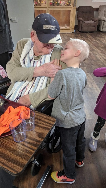 """ABOVE: A student at Cumbernauld Little Vikes, an intergenerational preschool class, leans on a """"grandpa,"""" the nickname for Cumbernauld Village residents who volunteer in the classroom. (Contributed photo)"""