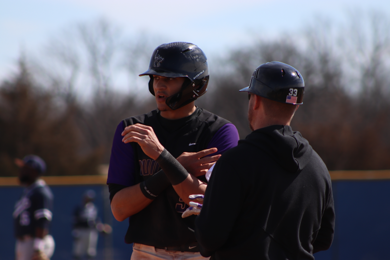 Cody Carpenter, senior outfielder, discusses something with Josh Kiel, assistant coach. Carpenter walked to first base after the drop third strike rule took effect at the top of the fourth inning. (Taylor Rodriguez/Staff photographer)