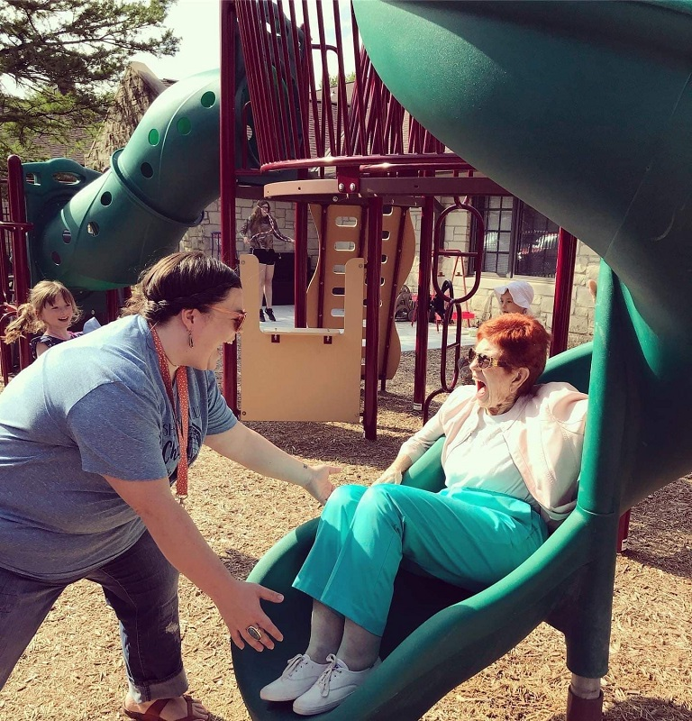 """ABOVE: Tabatha Rosproy, alumna, smiles with a """"grandma"""" at the Cumbernauld Little Vikes playground. The classroom is intergenerational, providing students with multiple contact opportunities each day with residents of Cumbernauld Village. (Contributed photo)"""