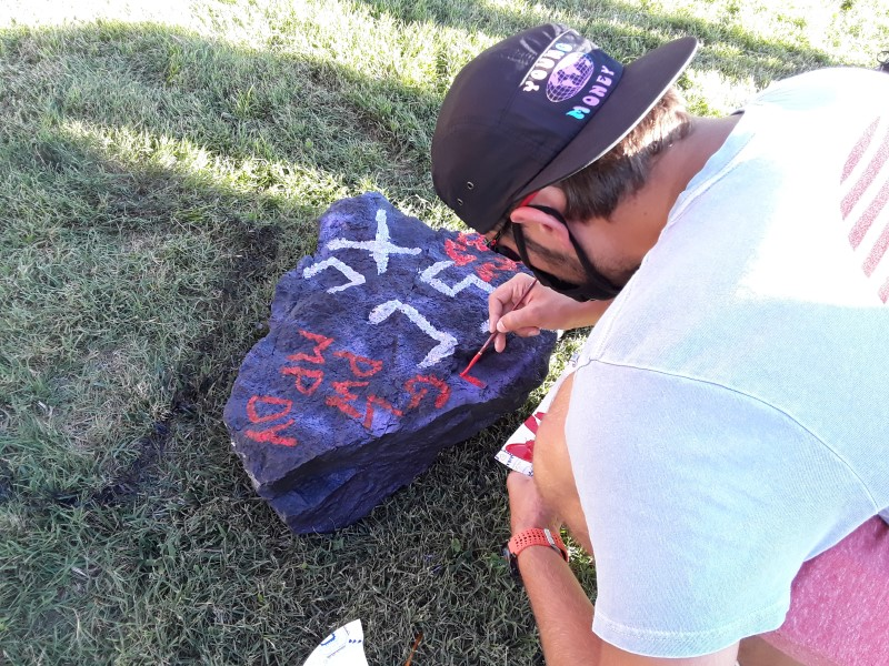 Maliki Pope, business administration junior, carefully marks his rock. Pope flashed his artistic side while painting.(Taylor Rodriguez/Staff photographer)