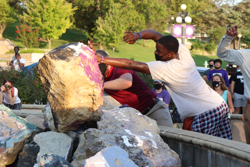 Two members of the football team give one final heave to their mountainous rock. They finished last season with a record of 5-6, and 5-5 in the KCAC. (Taylor Rodriguez/Staff reporter)