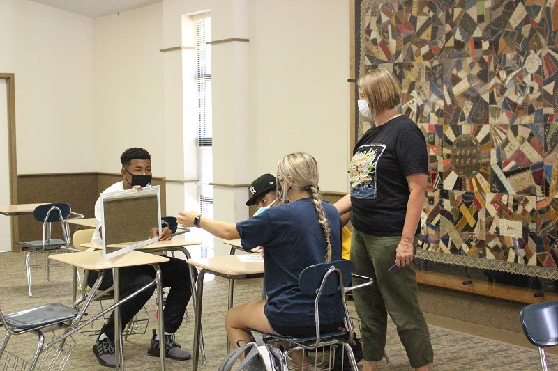Cheryl Rude, associate professor of leadership studies, helps students during an exercise. The exercise consisted of using a mirror to trace an image without being able to directly look at what one was tracing. (Lauren Sieh/Staff photographer)