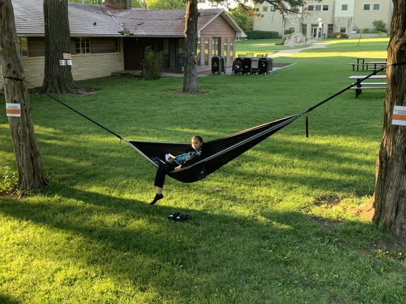 Chloe Manly, biochemistry senior, studies while relaxing in a hammock. Manly's hammock is one of many that can be found around campus. (Drake Vittitow/Staff photographer)