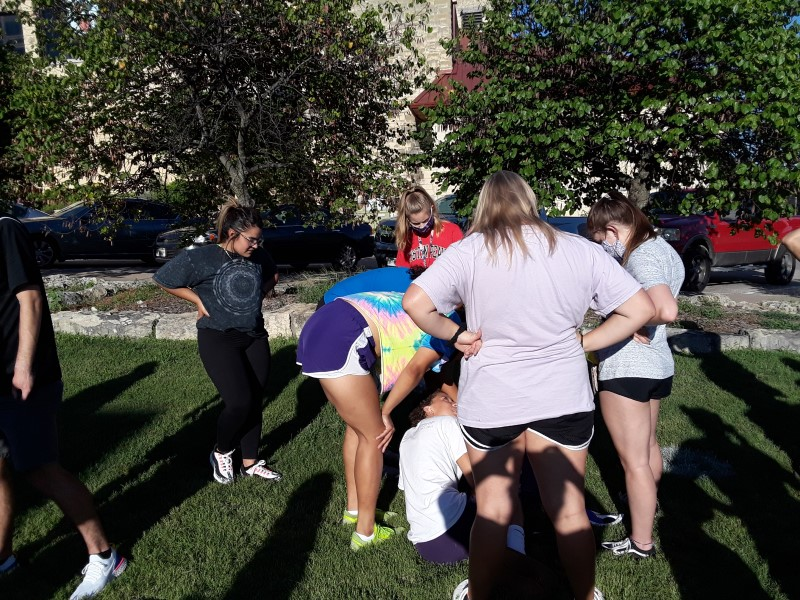 The women track and field team bond over painting their rock. Most teams have painted rocks for previous Moundbuilding ceremonies.(Taylor Rodriguez/Staff photographer)
