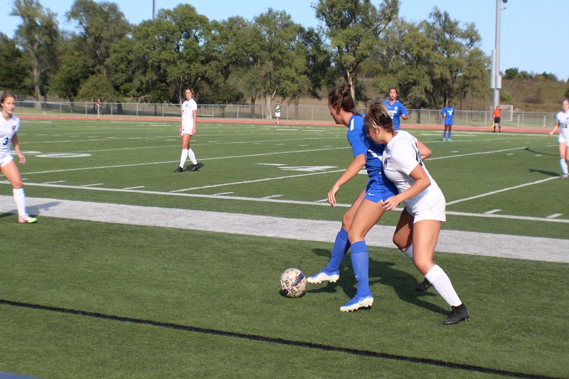 Lillian Grisso, freshman midfielder, guards a Tabor Bluejay in pursuit of the ball. Grisso looks for an opportunity to steal the ball from her opponent. (Lex Gouyton/ Staff photographer)