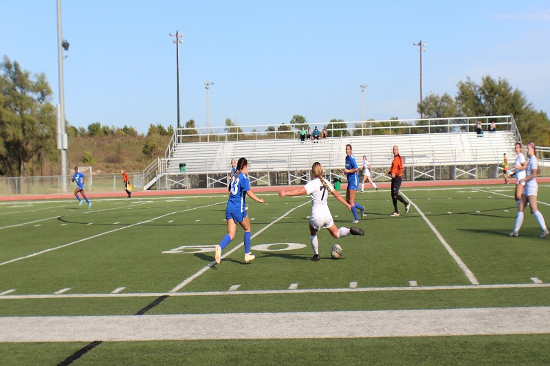 Sierra Salsman, senior defender, goes to pass the ball to a teammate up field against Tabor. The Bluejays look to swarm Salsman, but she manages to get the ball to a teammate. (Lex Gouyton/ Staff photographer)