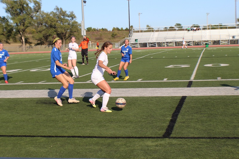Hailey Rouse, sophomore midfielder, defends the ball against a pack of Bluejays. Morgan Mitchell, junior midfielder, watches as Rouse heads up field. (Lex Gouyton/ Staff photographer)
