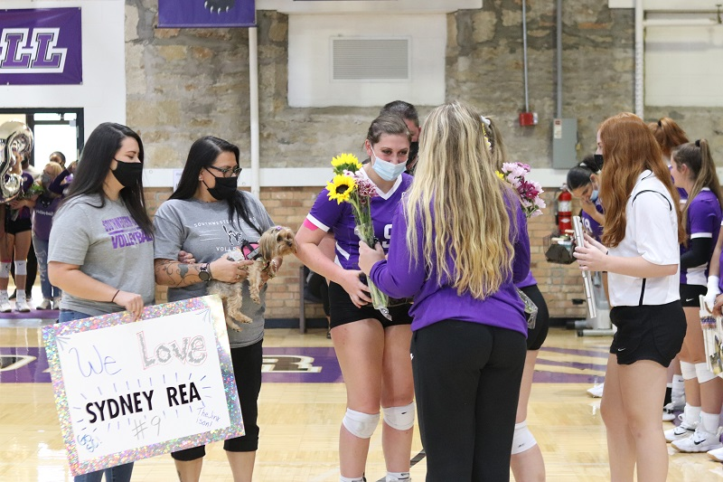 Sydney Hancock, senior setter, accepts gifts from the Lady Builder volleyball team. Hancock was joined by Sam Hancock, Justine Hancock and Kayla Van Hee. (Lauren Sieh/Staff photographer)