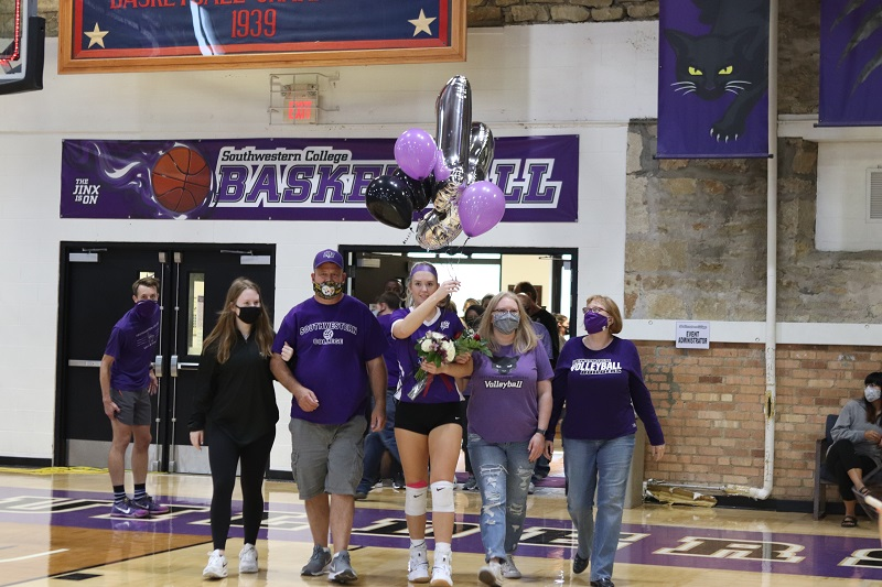 Lyxi Blaker, senior middle hitter, is escorted by her family. Blaker had the most attempts, 20, and kills, seven, of the night. (Lauren Sieh/Staff photographer)