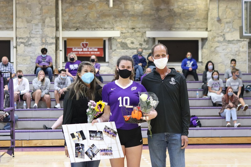 Jacquelyn Bogner, senior outside hitter, joins her mom and dad for a picture. Bogner took a total of seven attempts and gained one kill. (Lauren Sieh/Staff photographer)