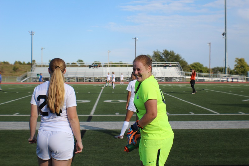 Morgan Mitchell, junior midfielder, and Ashley Soderlund, sophomore goal keeper, wait to enter the game. Soderlund cheeses as she is ready to play. (Lex Gouyton/ Staff photographer)