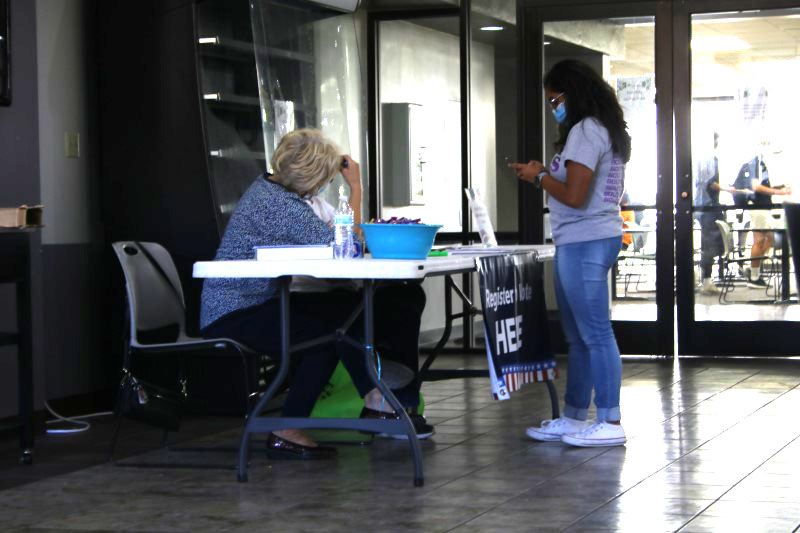 Selci Hopkins, psychology junior, has assistance as she double checks to make sure she registers correctly. Registering can be done online. (Brandon Hollis/Staff Photographer)
