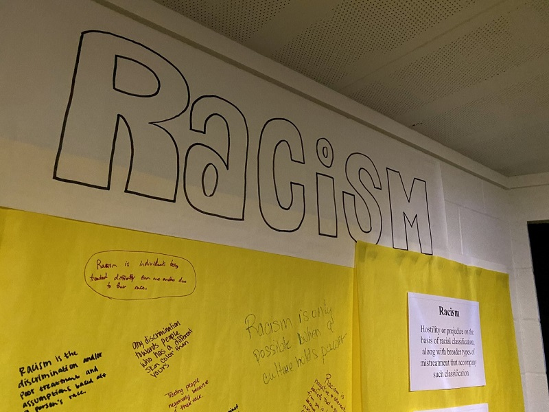 This section was titled racism. It had definitions of what racism was on the sides and how it affected people. The yellow paper was used for people to write and define what they think racism is. (Mallory Graves/Staff photographer)