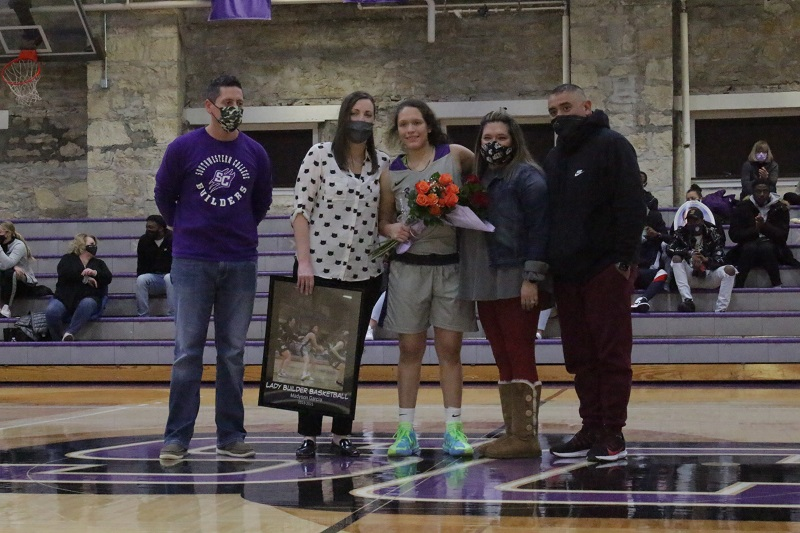 Madyson Garcia, senior guard, poses for a picture with her coach and family.  Her family came down to support her for senior night. (Mallory Graves/ Staff photographer)