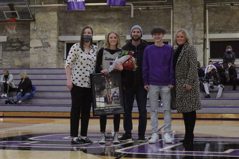 Sydney Webb, senior guard, stands with her family on senior night. She is currently out due to an injury. (Mallory Graves/ Staff photographer)