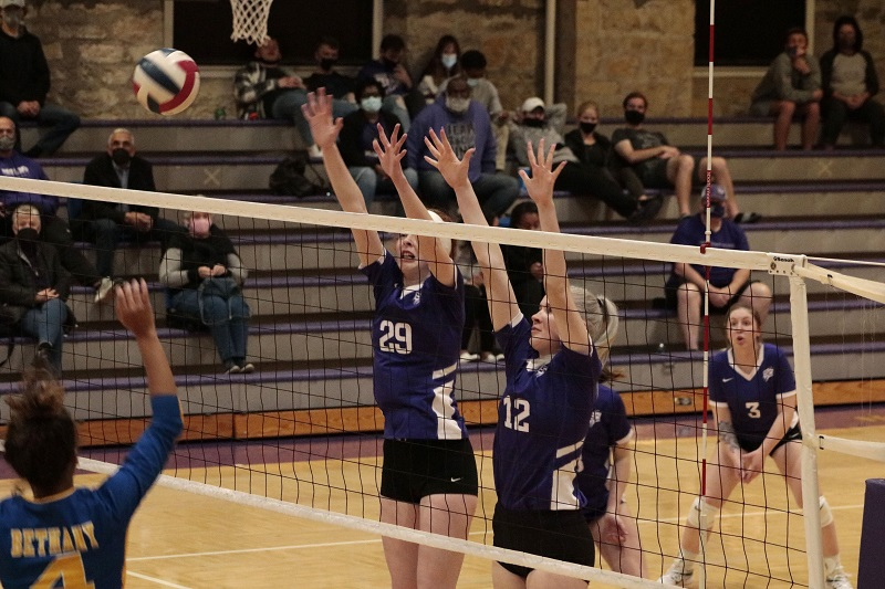 Faith Smith, freshman middle hitter (left), KaSandra Lyons, freshman outside hitter/ right-side hitter (right), jumps up to defend the opponents attack. (RJay McCoy/Staff photographer)