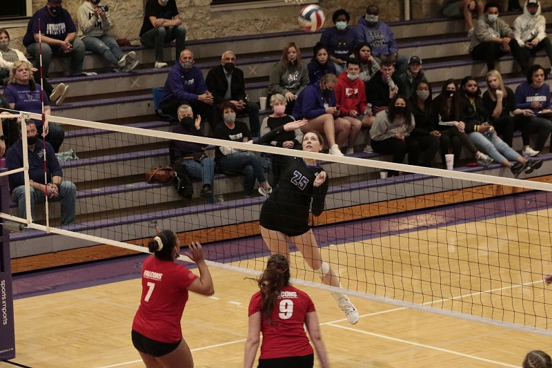 Morgan Harral, junior middle hitter, goes up to finish a kill. She had a combined ten kills on the night. (RJay McCoy/Staff photographer)
