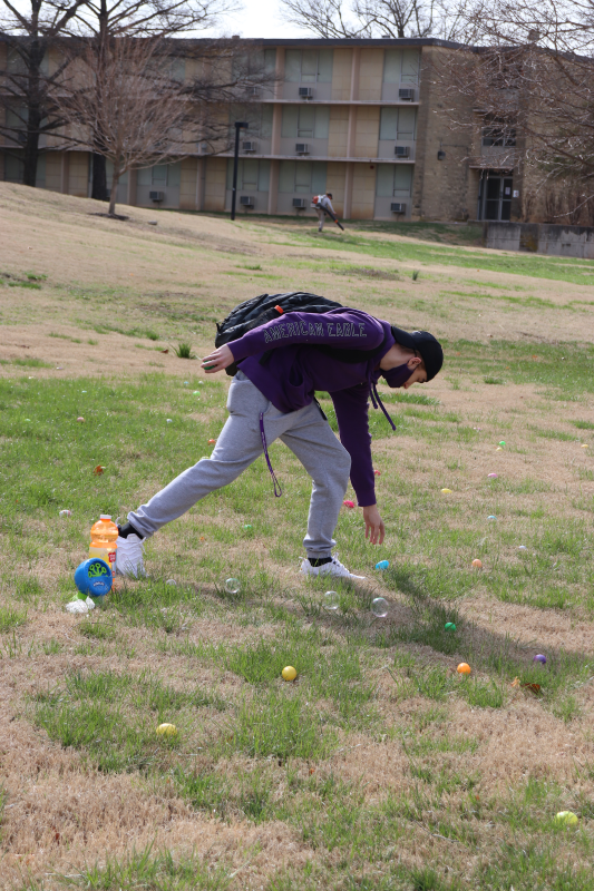 Christian Strella, athletic training freshman, reaches for his first egg. Strella won chocolate ina ll three of his eggs. (Taylor Rodriguez/Staff photographer)