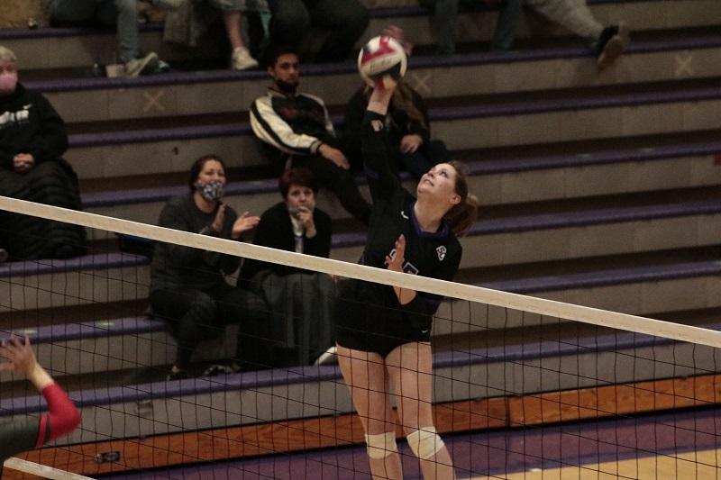 Morgan Harral, junior middle hitter, goes to finish on a kill attempt. She had a combined six kills for the night. (RJay McCoy/Staff photographer)
