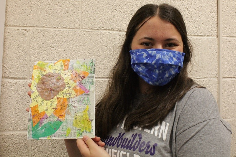 Carly Redding, philosophy and religion sophomore, holds up her artwork. She enjoyed taking some time off from studying. (Mallory Graves/Staff photographer)