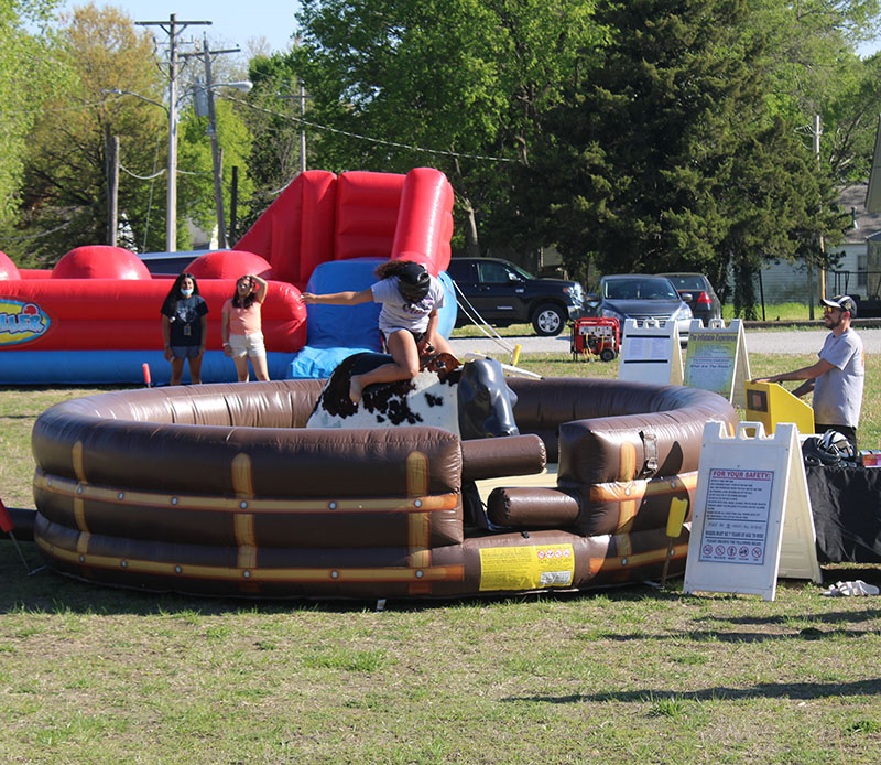 Paiden Bell, accounting freshman, rides the mechanical bull. Many individuals did so, as they were timed on how long they could last. (Daegiona Wilson/Staff photographer)