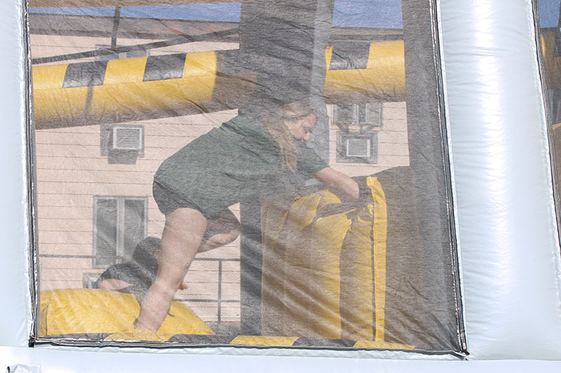 Two women race through the obstacle course inflatable. The inflatable was roughly 100 yards long, that stretched across Sutton Hall's lawn. (Daegiona Wilson/Staff photographer)