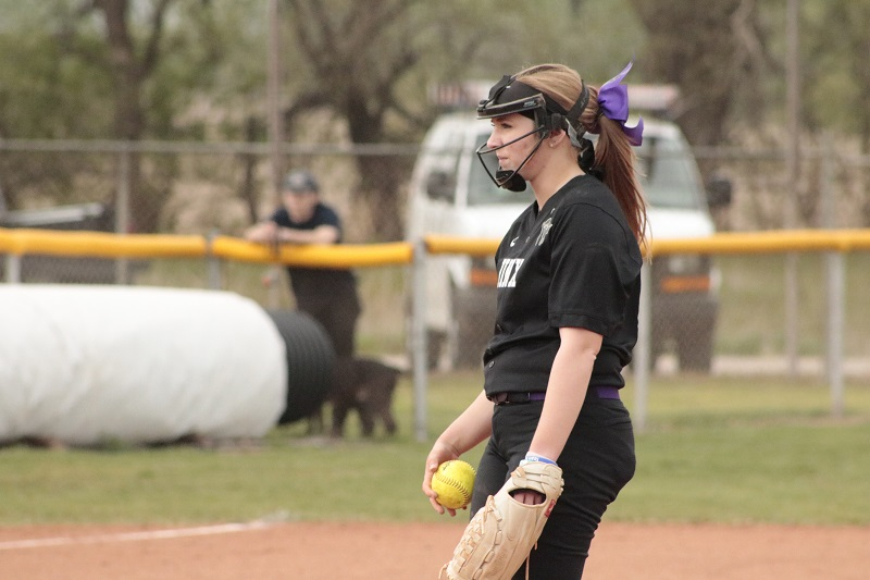 Hannah Foltz, senior pitcher, sizes up her competition before delivering the pitch. She pitched six innings in game two. (RJay McCoy/Staff photographer)
