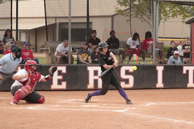 Julie Long, junior infielder, hacks at an incoming pitch. Long had two hits on the day series against Friends. (RJay McCoy/Staff photographer)