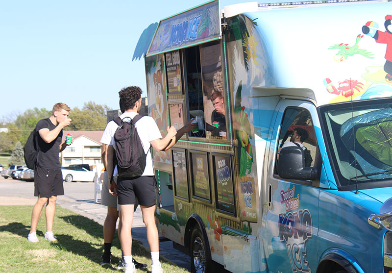 The men enjoy free Kona Ice. Along with Kona Ice, Uno Mas and Funky Monkey Munchies, were food trucks that attended this year's annual Block Party. (Daegiona Wilson/Staff photographer)