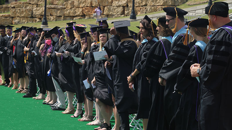 Students of Southwestern College's class of 2020 stand while flipping their tassel signifying being graduated. A live person commencement was held on May 8, 2021 to honor these graduates, as last year's live commencement was postponed. (Staff Photographer/ Daegiona Wilson)