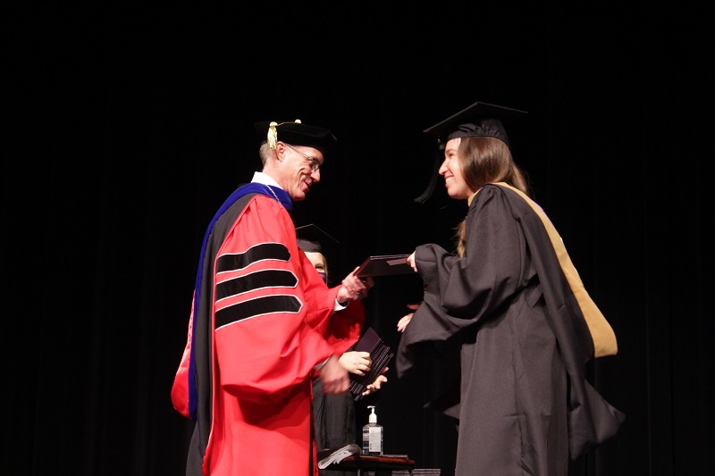 Elyse Achenbach shakes the president's hand as she receives her Master of Business Administration. She served as the residence director for Broadhurst Hall. (Mallory Graves/Staff photographer)