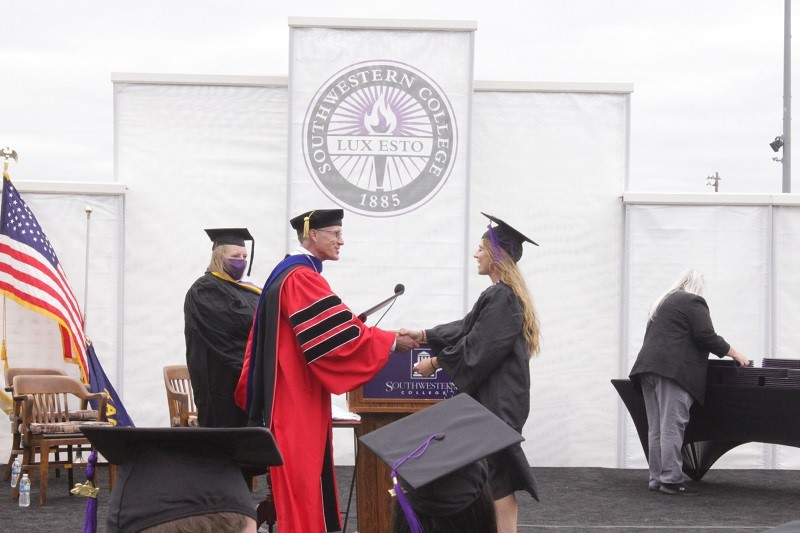 Kayleen Gonzalez shakes hands with Brad Andrews, college president, when receiving her diploma. She double majored in psychology and business administration. (Mallory Graves/Staff photographer)