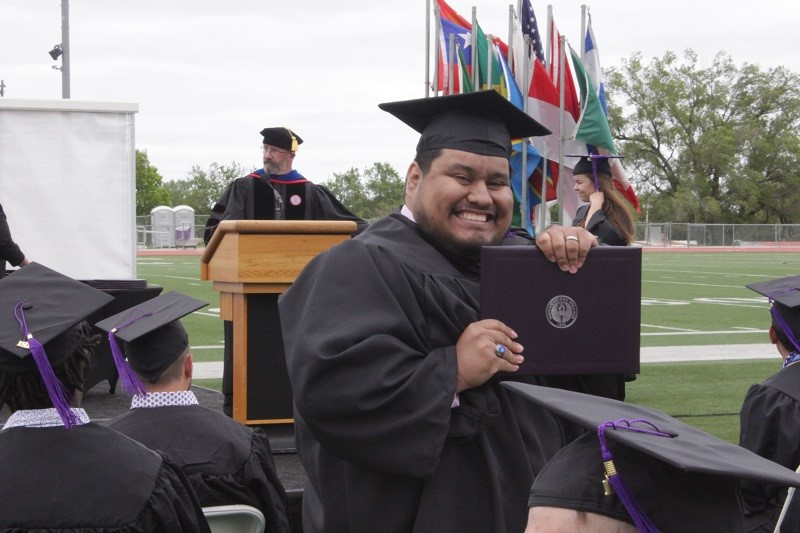Jose-Carlos Fuentes shows his pearly whites with his diploma in hand. He graduated with a degree in communication with an emphasis in film studies and production. (Mallory Graves/Staff photographer)