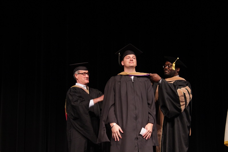 Owen Breithaupt proudly awaits to be hooded. He obtained his Master of Business Administration. (Mallory Graves/Staff photographer)