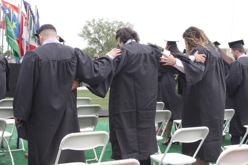 Three men represent the meaning of what it means to be a part of the Builder family. They did this during a prayer at graduation. (Mallory Graves/Staff photographer)