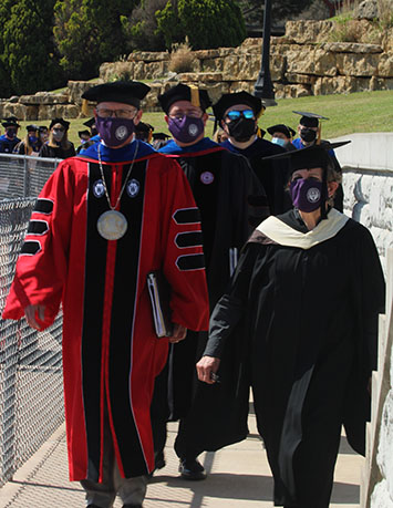 Dr. Bradley Andrews, president, and Allyson Moon, associate professor of theatre and speech, lead professors and the class of 2020. Commencement was held in May 8, 11 a.m. at Jantz Stadium. (Staff Photographer/ Daegiona Wilson)