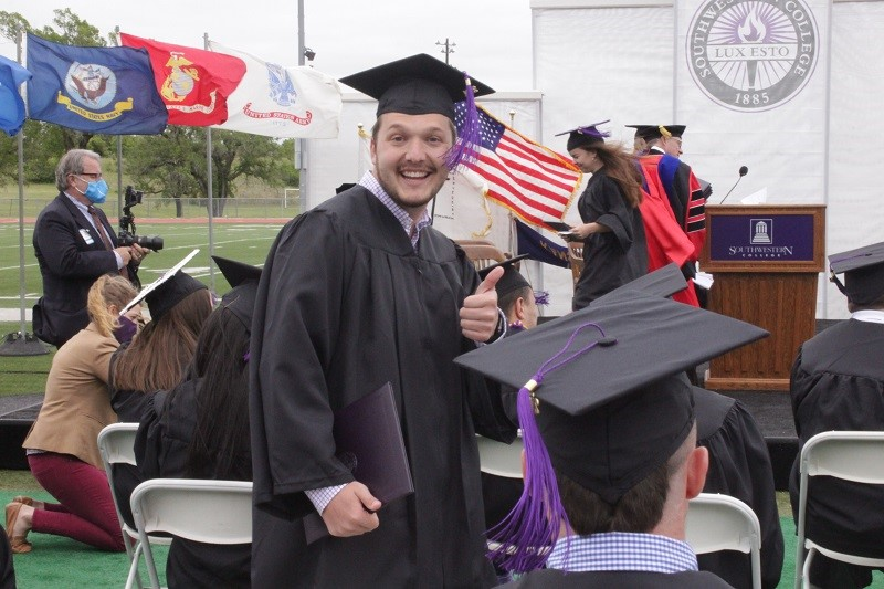 Samuel DeNike gives a thumbs up for his accomplishment as a recent college graduate. He graduated with a degree in psychology. (Mallory Graves/Staff photographer)
